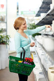 Woman with basket choosing flower pot in shop Royalty Free Stock Images