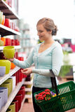 Woman with basket choosing flower pot in shop Stock Photo