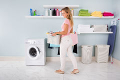 Woman With Basket Of Clothes In Utility Room. Young Smiling Woman With Basket Of Clothes Near Washing Machine In Utility Room Royalty Free Stock Images