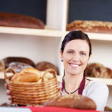 Woman with a basket of fresh rolls. Beautiful smiling woman working in a bakery with a basket of fresh rolls in her hands looking at the camera, focus to her Royalty Free Stock Photo