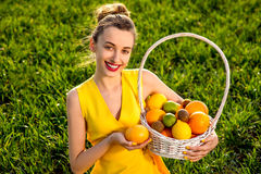 woman with basket of fruits on green field Royalty Free Stock Photo