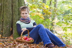 Woman with a basket full of red apples Stock Photo