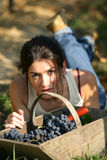 Woman with basket of grapes. Woman lying on her stomach next to a basket of grapes Royalty Free Stock Photo