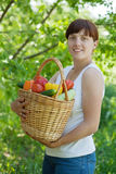 Woman with basket of harvested vegetables Stock Images