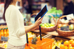 Woman with basket and tablet pc in market Stock Image