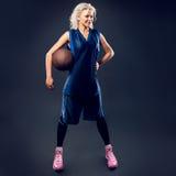 Woman basketballer in blue jersey. In studio Stock Photos