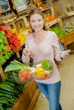 Woman with basketful fruits and list Stock Photos