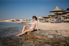 Woman basking in the sun. Red Sea shore. Beach with umbrellas Stock Photo
