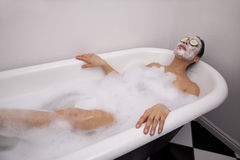 Woman in bath with cream on face Stock Images