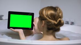 Woman in bath holding tablet PC, watching online video channel, back view stock video footage