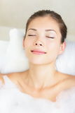 Woman in bath relaxing. Closeup of young asian woman in bathtub bathing with closed eyes Royalty Free Stock Photos