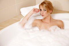 Woman in bath relaxing. Closeup of young woman in bathtub bathin. Attractive blonde woman in bath relaxing. Closeup of young woman in bathtub bathing Royalty Free Stock Images