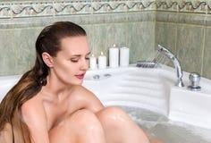 Woman in bath relaxing. Young beautiful woman washing body in a bath Royalty Free Stock Photography