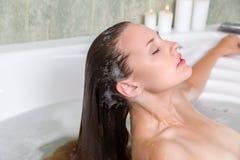 Woman in bath relaxing. Young beautiful woman washing hair in a bath Royalty Free Stock Photography