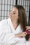 Woman in a bath robe brushing her hair Royalty Free Stock Image