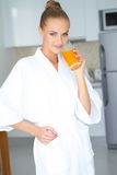 Woman in bath robe drinking orange juice Stock Photo