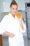 Woman in bath robe drinking orange juice Stock Photo