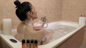 Woman in the bath with a sponge is washed back. In room stock video