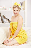 Woman in bath towel. Interior portrait of beautiful young blonde size plus woman model in yellow bath towel sitting on sofa royalty free stock images