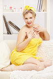 Woman in bath towel. Interior portrait of beautiful young blonde size plus woman model in yellow bath towel sitting on sofa royalty free stock photo
