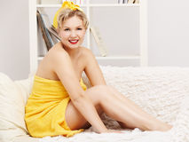 Woman in bath towel. Interior portrait of beautiful young blonde size plus woman model in yellow bath towel sitting on sofa stock photo