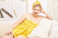 Woman in bath towel. Interior portrait of beautiful young blonde size plus woman model in yellow bath towel sitting on sofa stock photos