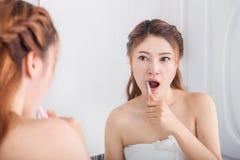 Woman in bath towel brushing teeth with mirror in bathroom Royalty Free Stock Photos