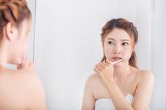 Woman in bath towel brushing teeth with mirror in bathroom Stock Photography