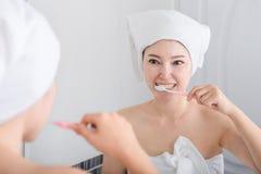 Woman in bath towel brushing teeth with mirror in bathroom Royalty Free Stock Photography