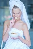 Woman in Bath Towel Eating Snacks from Bowl Royalty Free Stock Photo