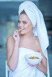 Woman in Bath Towel Eating Snacks from Bowl Stock Image