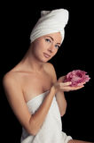 Woman after bath with towel and flower. Isolated on black Royalty Free Stock Photos