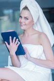 Woman in Bath Towel Holding Tablet Computer Royalty Free Stock Photos