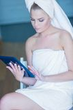 Woman in Bath Towel Looking at Tablet Computer Royalty Free Stock Images