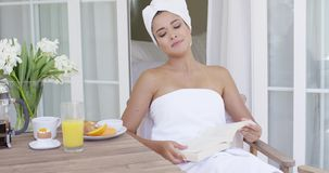 Woman in bath towel reading book at table stock video footage