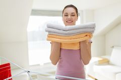 Woman with bath towels and drying rack at home. Laundry, freshness and household concept - happy woman or housewife with drying rack holding fresh bath towels at Royalty Free Stock Image