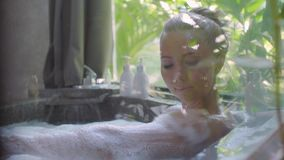 Woman in Bath Tub. Young,beautiful woman relaxing in the bath with a foam.Pretty girl bathing with pleasure in bathroom with a window and spending time in luxury stock footage
