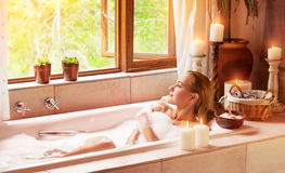 Woman bathing with pleasure. Lying down in the tub with foam and looking in the window, spending time in luxury spa resort Royalty Free Stock Images