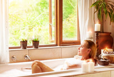 Woman bathing with pleasure. Lying down in the tub with foam and looking in the window, spending time in luxury spa resort Royalty Free Stock Image