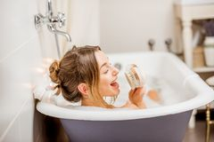 Woman bathing at the retro bathroom stock photography