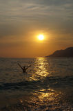 Happy bathing at sunset. Woman bathing in the sea at golden sunset in Croatia Royalty Free Stock Photo