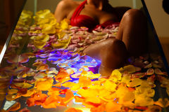 Woman bathing in spa with color therapy. The bathtub is lit with colorful lights, lots of flower petals on tub royalty free stock images