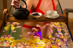 Woman bathing in spa with color therapy. The bathtub is lit with colorful lights, lots of flower petals on tub and tea stock photo