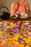 Woman bathing in spa with color therapy. The bathtub is lit with colorful lights, lots of flower petals on tub and tea stock photography