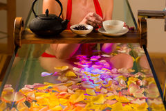 Woman bathing in spa with color therapy. The bathtub is lit with colorful lights, lots of flower petals on tub and tea stock images