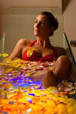 Woman bathing in spa with color therapy. The bathtub is lit with colorful lights, lots of flower petals on tub royalty free stock photo