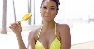 Woman in bathing suit eating mango ice pop stock footage