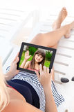 Woman in a bathing suit lying on a chaise lounge with a tablet a Royalty Free Stock Images