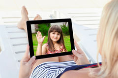 Woman in a bathing suit lying on a chaise lounge with a tablet a. Woman in a bathing suit lying on a chaise lounge with a computer tablet and communicates by royalty free stock photography