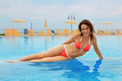 Woman in bathing suit sitting in pool stock images